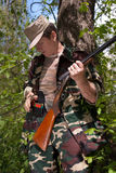 Hunter with gun in hands. In forest royalty free stock photo