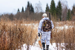 Hunter with gun on snowy field Royalty Free Stock Image
