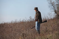 Hunter with a gun on steppe slope Royalty Free Stock Photo