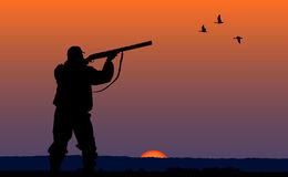 Hunter with gun at sunset background. Silhouette of man on the hunting Stock Image