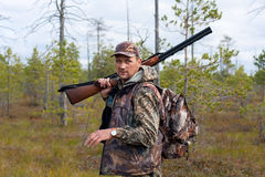 Hunter with gun on the swamp. Hunter walking with gun on the swamp Stock Photo
