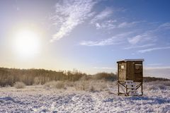 Hunter high seat in a snow covered winter landscape against a blue sky with a warm sun, copy space royalty free stock photography