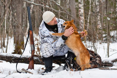 Hunter with his dog during the rest on winter hunting Stock Image