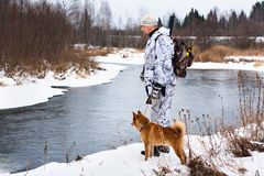 Hunter with his dog on the river bank Stock Photography