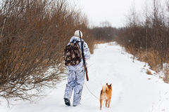 Hunter with his dog walking on the winter road Stock Images