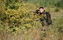 Hunter hold rifle. Man wear camouflage clothes nature background. Hunting permit. Hunting is brutal masculine hobby. Hunting equipment for professionals royalty free stock image