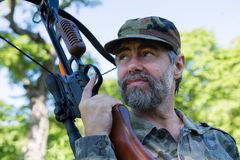 Hunter holding a crossbow. In the woods Stock Images