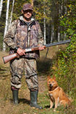 Hunter holding a gun with his dog royalty free stock photo