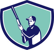 Hunter Holding Shotgun Rifle Crest Retro. Illustration of a hunter wearing hat holding shotgun rifle looking to the side set inside shield crest on isolated Stock Photo