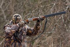 Hunter during a hunt. Hunter in camouflage takes aim from a gun Royalty Free Stock Photography