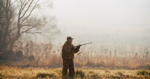 Hunter in hunting equipment aim the target with rifle in the field at foggy morning or sunny autumn evening