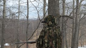 The hunter in the hut of the branches. A hunter in a hut from the branches looks out for prey. Aims a gun stock video