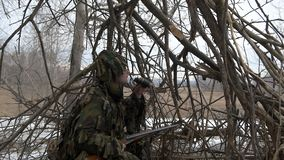 The hunter in the hut of the branches. A hunter in a hut from the branches looks out for prey with binoculars stock video footage