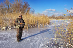 Hunter on the ice pond waiting victim. Royalty Free Stock Photography