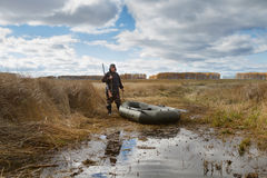 Hunter. And inflatable boat on the shore of the lake overgrown with reeds Royalty Free Stock Photos