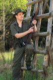 Hunter leaning on a tree stand Royalty Free Stock Photo