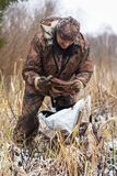 Hunter with leghold trap. Hunter preparing leghold trap for setting on the riverbank Stock Photo