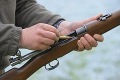Hunter loading rifle Royalty Free Stock Image