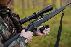 Hunter loading rifle stock photo