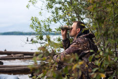 Hunter looking through binoculars on the river Stock Image