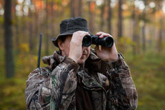 Hunter looking into binoculars. Hunter in the woods looking into binoculars Stock Photography