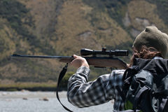 Hunter looking through rifle aim Royalty Free Stock Photos