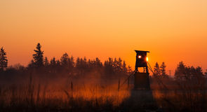 Hunter lookout tower on the edge of the forest. In the morning mist Royalty Free Stock Photo