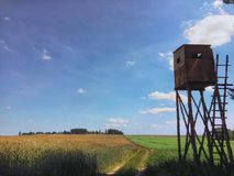 Hunter lookout tower in a field. Nothern Poland landscape, wooden hunter lookout tower , field path and wheat meadow Royalty Free Stock Photography