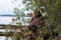 Hunter looks through the binoculars at the river Stock Photography