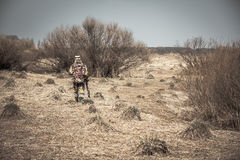 Hunter man in camouflage with gun going through rural area with dry grass and bushes during hunting. Hunter man in camouflage with gun going through rural field stock photography