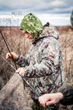 Hunter man in camouflage installing hunting tent in overcast day during hunting season Stock Images