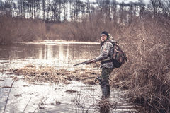 Hunter man creeping in swamp during spring hunting season Royalty Free Stock Photography