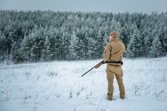 Hunter man dressed in camouflage clothing standing in the winter. Hunter man dressed in camouflage clothing  in the winter pine forest. Armed with a rifle Stock Photos