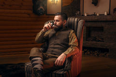 Hunter man drink alcohol after successful hunt. Hunter man in traditional vintage hunting clothing drink luxury alcohol after successful hunt. Fireplace, stuffed Stock Image