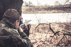 Hunter man with gun aiming and prepared to make a shot during hunt Royalty Free Stock Photography