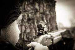 Hunter man with gun aiming and prepared to make a shot during hunting. In black and white colors stock photos