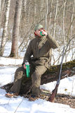Hunter man is having rest and drinking tea in the forest Royalty Free Stock Photos