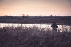 Hunter man in rural field in expectation of hunting during sunrise with copy space Stock Images