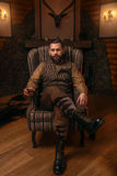 Hunter man sitting in a chair and drink whiskey stock images