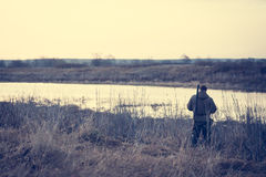 Hunter man standing at river bank in expectation of successful hunting stock photography