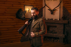 Hunter man in vintage clothing with antique rifle. Respectable hunter man in vintage stylish hunting clothing with antique rifle against fireplace. Stuffed wild Royalty Free Stock Photos