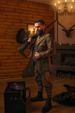 Hunter man in vintage clothing with antique rifle. Respectable hunter man in vintage stylish hunting clothing with antique rifle against fireplace. Stuffed wild Royalty Free Stock Images