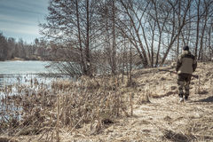Hunter man walking along river bank during spring hunting season. Hunter man walking along river bank during hunting season Royalty Free Stock Image