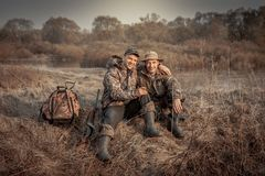 Hunter men friends recreation rural field hunting period symbolizing strong friendship. Hunter men friends resting in rural field during hunting period Royalty Free Stock Image