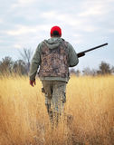 Hunter moving with shotgun looking for prey. Stock Image
