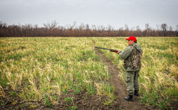Hunter moving with shotgun looking for prey. Hunter with a gun. Hunting for hare Stock Image