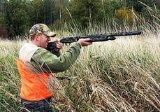 Hunter in orange safety vest. Hunter shooting gun in marsh grass wearing safety vest stock photo