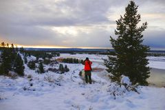 Hunter Overlooking Madison River, Montana. Winter on the Madison River, just west of Yellowstone, Montana.  Cloudy cold morning looking downriver.  A hunter Royalty Free Stock Photography