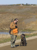 Hunter with a pheasant and his dog Royalty Free Stock Image