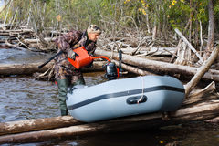 Hunter pouring fuel into a tank of his boat. From a red canister Stock Photo